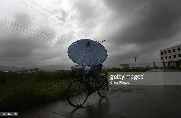 A woman makes her way in the rain before typhoon Sepat makes landfall in the neighboring Fujian Province August 18 2007 in the Cangnan County of...