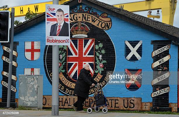 A woman makes her way past election posters for Gavin Robinson of the DUP on May 7 2015 in Belfast Northern Ireland The United Kingdom has gone to...
