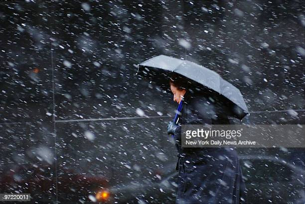 A woman makes her way through a messy mix of snow and sleet at First Ave and E 72nd St