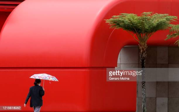 Woman makes her way through the rain outside the Resnick Exhibition Pavilion at the Los Angeles County Museum of Art in Los Angeles on May 18, 2020....
