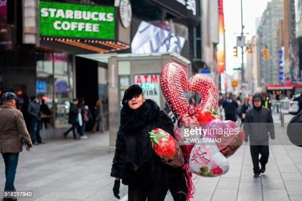 A woman makes her way with Valentine's Day balloons in New York on February 14 2018 PHOTO / Jewel SAMAD