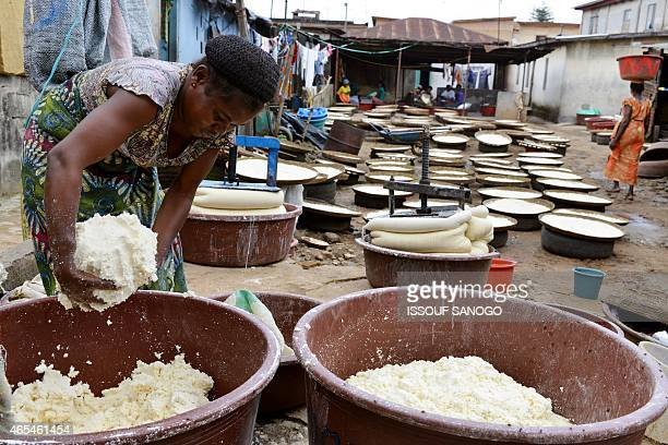 A woman makes manioc flour in Abidjan on March 6 for the preparation of the Attieke a classic of the Ivorian food Originated from southern Ivory...