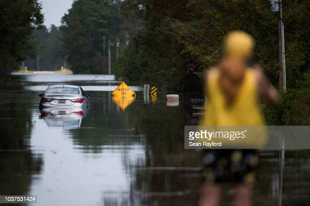 A woman makes photos of a disabled car in floodwaters caused by Hurricane Florence near the Todd Swamp on September 21 2018 in Longs South Carolina...