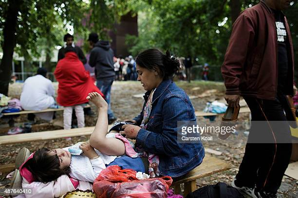 A woman makes the baby a new diaper in the Horst Korber Sportcenter on September 10 2015 in Berlin Germany Approximately 500 migrants arrived on the...