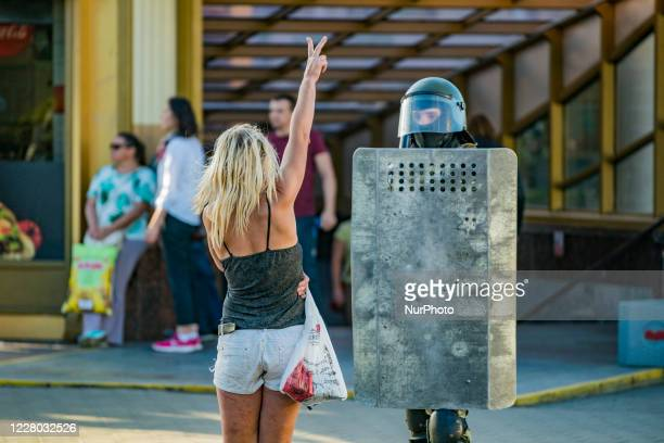 Woman makes the victory symbol in front of a riot policeman in Minsk, Belarus, on August 11 symbol against the government after the claimed...