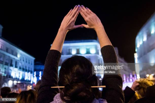 A woman makes the women sign with her hands during a demonstration for the International Day for the Elimination of Violence Against Women