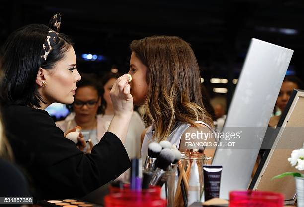 A woman makes up a girl during the Get Beauty fair a beauty and fashion fair inspired by the US 'Beautycon' event gathering of fashion bloggers and...