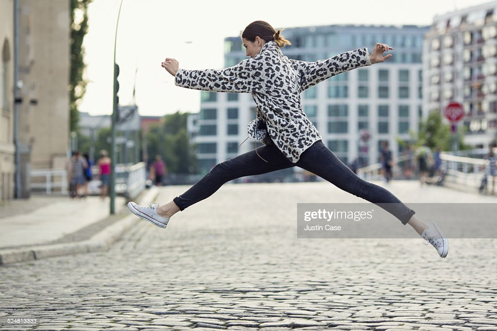 woman making a big jump in a sunny city street : Stock Photo