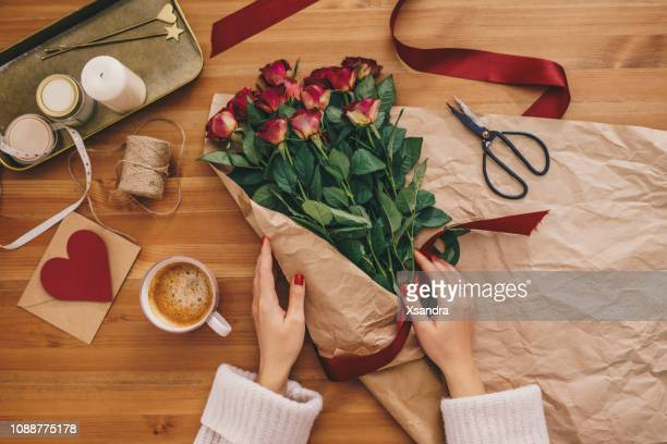 woman making a bouquet of red roses - valentine card stock photos and pictures