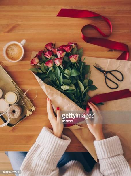 donna che fa un bouquet di rose rosse - mazzo di rose foto e immagini stock