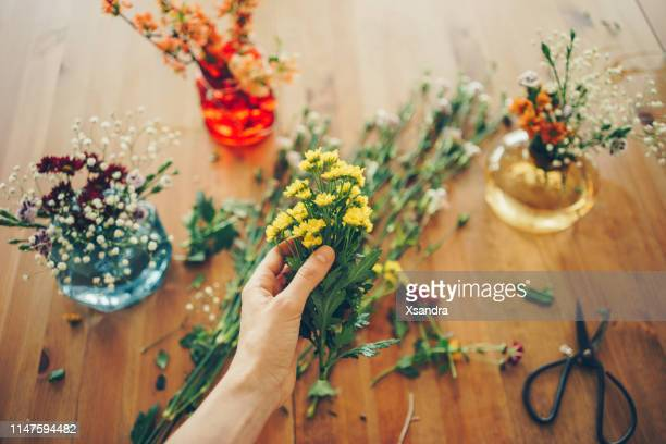woman making a bouquet of spring flowers - arranging stock pictures, royalty-free photos & images