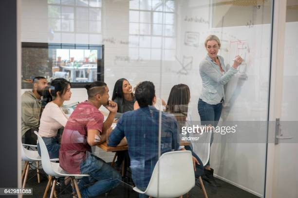woman making a business presentation at the office - employee engagement stock pictures, royalty-free photos & images