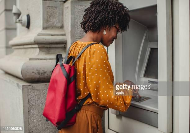 frau macht bargeld an geldautomaten - geldautomat stock-fotos und bilder