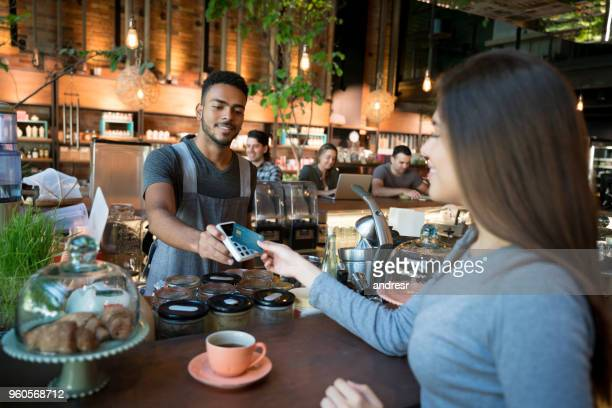 woman making a contactless payment at a restaurant - nfc stock pictures, royalty-free photos & images