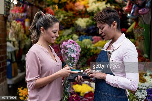Woman making a contactless payment at the florist