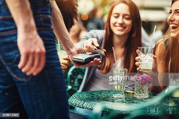 woman making a contactless payment with her phone - money transfer stock pictures, royalty-free photos & images
