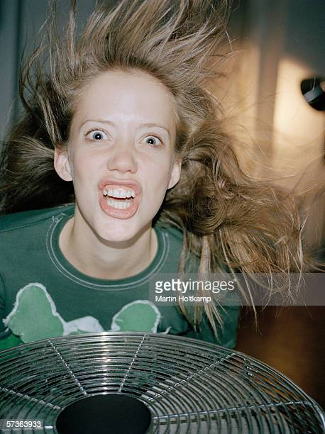 A woman making a crazy face above a fan