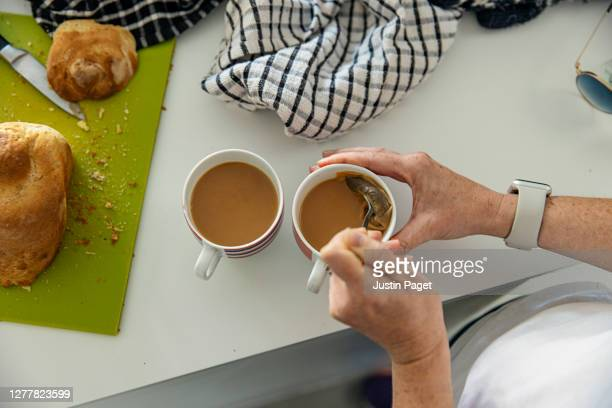 woman making a cup of tea - making stock pictures, royalty-free photos & images