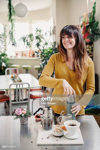 A woman making a flask of coffee in a kitchen.