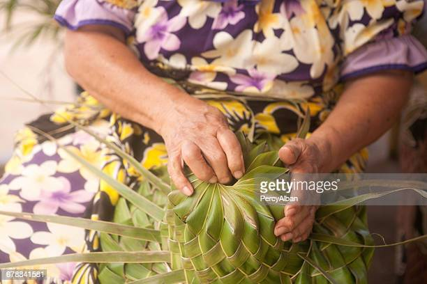 Woman making a hat from palm leaves