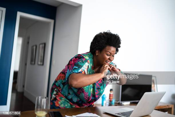 woman making a heart shape with her hands during a video call at home - social media followers stock pictures, royalty-free photos & images