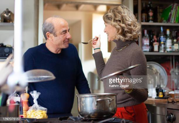 woman making a hearty soup, having her husband taste from spoon - wife stock pictures, royalty-free photos & images