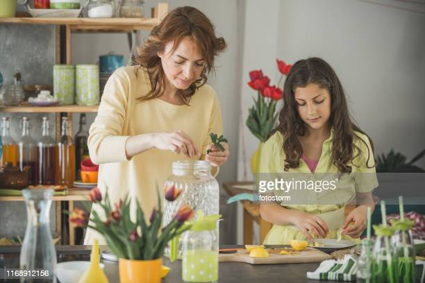 woman making a lemonade with her teenage daughter - mint plant family stock pictures, royalty-free photos & images