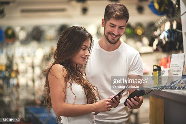 woman making a payment in bicycle store - megastore stock photos and pictures