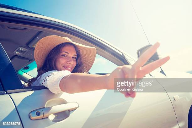 Woman making a peace sign while driving