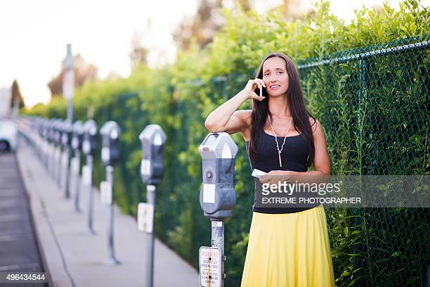 woman making a phone call next to parking meter - parking meter stock photos and pictures