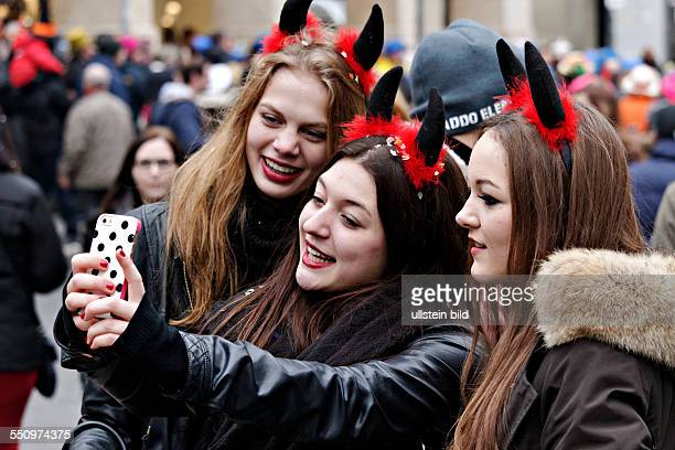 3 woman making a self portrait with mobile phone Fasching street party Munich Upper Bavaria Germany Europe