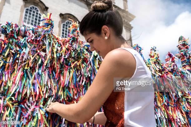 woman making a wish with brazilian ribbons on church fence in salvador, bahia, brazil - portafortuna foto e immagini stock