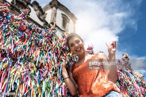 Woman making a wish with brazilian ribbons on church fence in Salvador, Bahia, Brazil