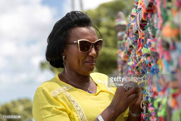 mulher que faz um desejo com fitas brasileiras em igreja nosso senhor do bonfim cerca da igreja em salvador, bahia, brasil - religião - fotografias e filmes do acervo