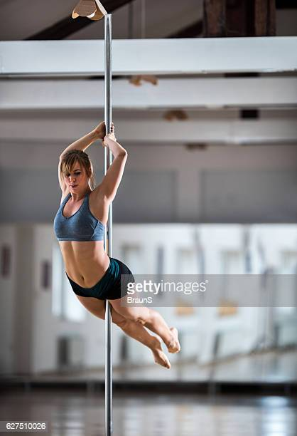 Woman making an effort while dancing on a pole.