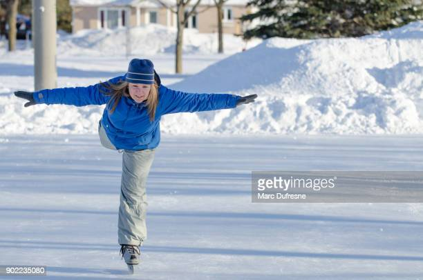 woman making arabesque while ice skating on an ice rink outdoors - figure skating stock pictures, royalty-free photos & images