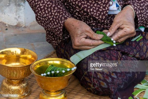 woman making bai sii decorations. - tim bewer stock pictures, royalty-free photos & images