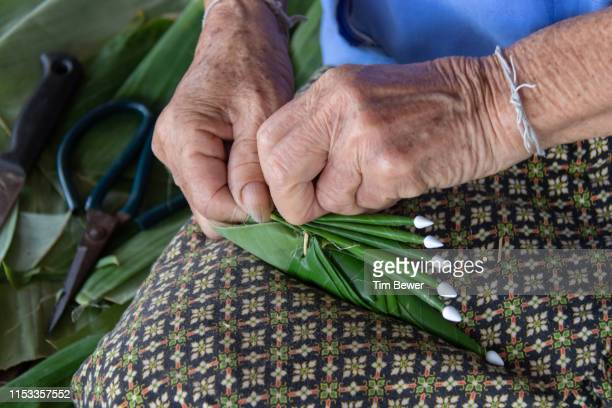 woman making bai sii from banana leaves. - tim bewer stock pictures, royalty-free photos & images
