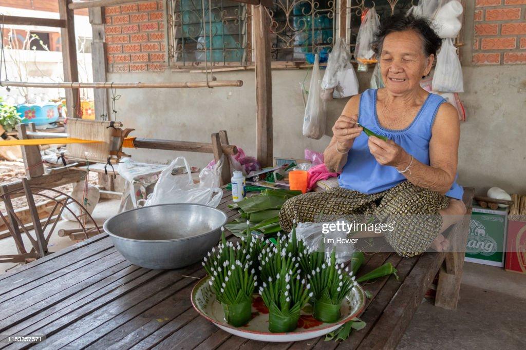 Woman making bai sii from banana leaves. : Stock Photo