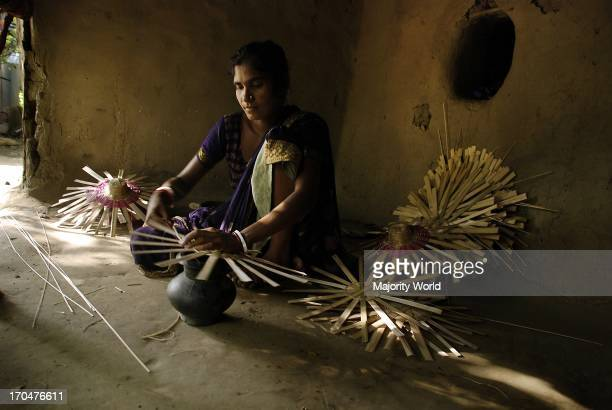 A woman making bottom part of bamboo baskets with strips of bamboo at her home in Chuadanga Bangladesh August 27 2008
