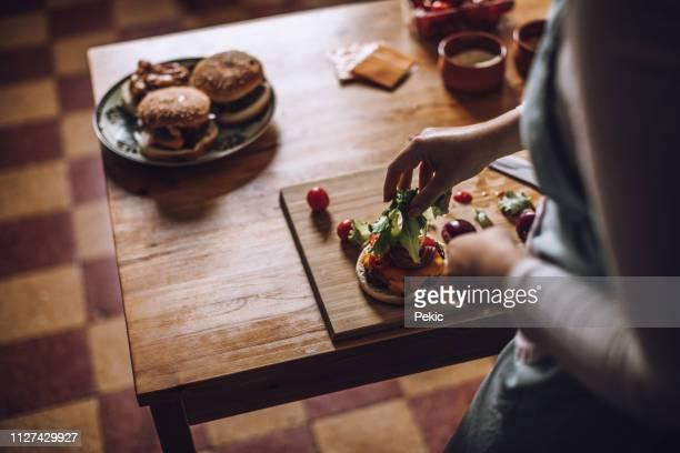 mulher que faz hambúrgueres mais suculento com vegetais frescos - hambúrguer - fotografias e filmes do acervo