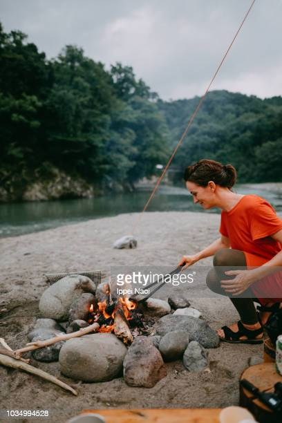 Woman making campfire by river, Japan