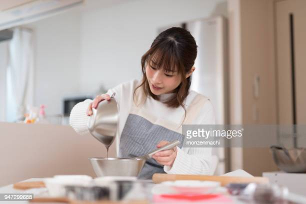 woman making chocolate pastry in kitchen - chocolate making stock pictures, royalty-free photos & images