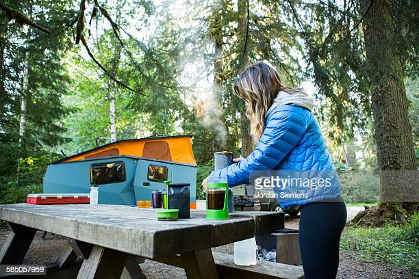 A woman making coffee at camp.