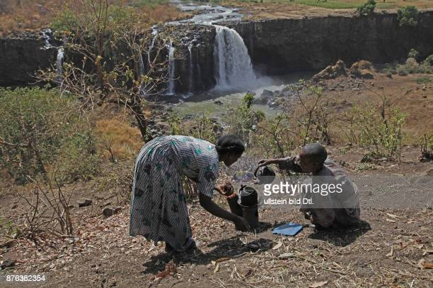 Woman making coffee for tourists by the source of the Blue Nile in the mountains near the Rift Valley in Ethiopia