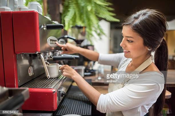 Woman making coffee in a machine