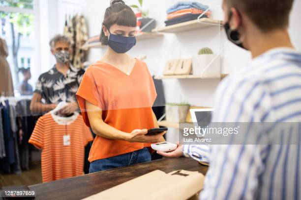 woman making contactless payment at clothing store - queuing stock pictures, royalty-free photos & images