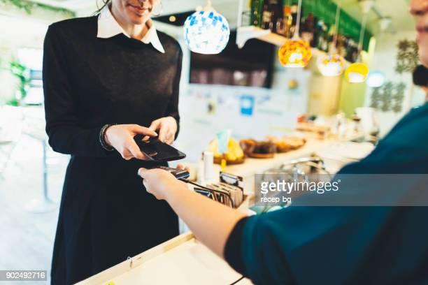カフェで非接触型決済を行う女性