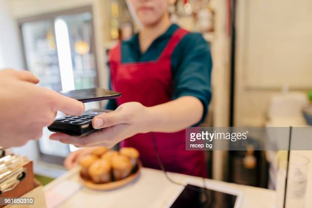woman making contactless payment in cafe - nfc stock pictures, royalty-free photos & images