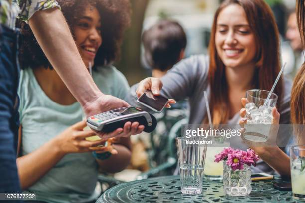 Woman making contactless payment with smartphone